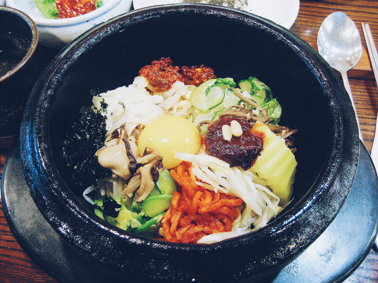A South Korea popular dish, Bibimbap is a mix of vegetables, egg, some meat, and is a common staple in a South Korean dinner table.